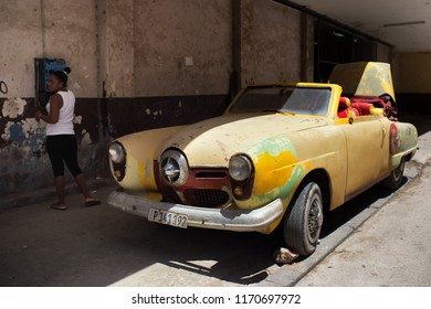 Havana, Cuba - July 18, 2017: 1950 Studebaker Champion convertible car with a lady at public phone in background, Calle Aguacate, Habana Vieja.