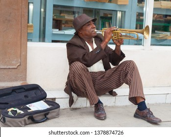 HAVANA CUBA - JULY 8; Street music  in Havana with Afro-Cuban man busking while sitting on footpath in front shop window playing trumpet July 8 2012 Havana Cuba