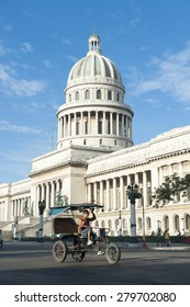 HAVANA, CUBA - JUNE, 2011: Bicycle taxi known locally as a bicitaxi pedals past the landmark Capitolio building.