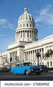 HAVANA, CUBA - JUNE, 2011: Classic American Cuban taxi car passes in front of the Capitolio building in Central Havana.
