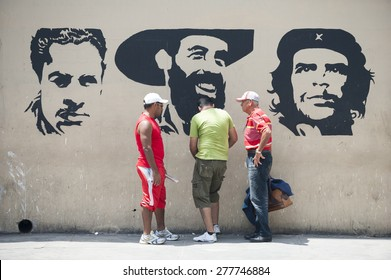 HAVANA, CUBA - JUNE, 2011: Trio of Cuban men huddle in front of propaganda mural featuring Julio Antonio Mella, Camilo Cienfuegos, and Che Guevara, three leaders of the Communist Revolution.