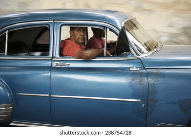 HAVANA, CUBA - JUNE, 2011: Vintage American car serving as taxi drives with passengers along the Malecon in Central Havana.