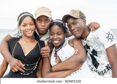 HAVANA, CUBA - JUNE, 2011: Young Cuban men and women stand together and smile as they pose for a photograph on the Malecon, a popular place for socializing.