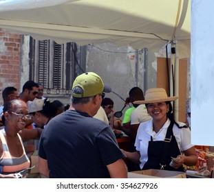 HAVANA, CUBA - JUNE 2015: A friendly Cuban lady serves customers in an open-air food market in Havana Central (Centro Habana) as part of the Biennale festival.