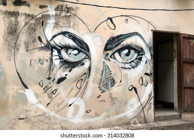 HAVANA, CUBA - JUNE 2015: Graffiti of a blue-eyed girl painted around a wall and a door.