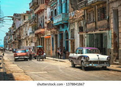 HAVANA, CUBA - June 2015 : Street scene with old cars and colorful buildings in Old Havana