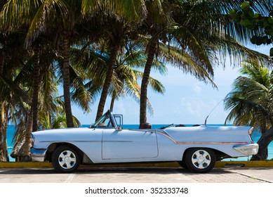 Havana, CUBA - JUNE 22, 2015: American white classic car cabriolet parked under palms near the beach in Havana Cuba