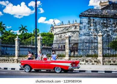 Havana, Cuba - June 27, 2017: HDR - American red Chevrolet Belair convertible classic car on the Malecon before a fortress el Morro and wait of tourists for a guiding tour in Havana Cuba - Serie Cuba
