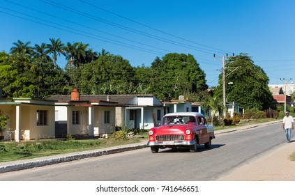 Havana, Cuba - June 27, 2017: American red Chevrolet with white roof classic car drives on the main street in the suburb from Havana Cuba