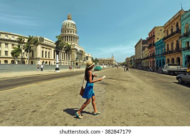 HAVANA, CUBA - June 29, 2015: A woman crosses the street with tourist map in hand near the Capitol building. Green retro car moves toward her. Vintage style photo