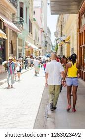 Havana / Cuba - June 6 2014:  - People walking on the streets of Havana, Cuba. Couple walking on Obispo street in Havana. Travel and adventure concept.