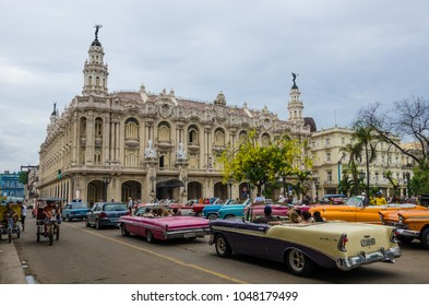 HAVANA, CUBA - JUNE 9, 2016: Colorful classic convertible cars are popular with tourists as they are driven in the La Habana Vieja neighborhood with the Gran Teatro in front of them.