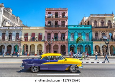 Havana, Cuba - Mar 10th 2018 - Classic image of Havana, with color everywhere, old cars in the street, people around, colonial houses in the background, blue sky