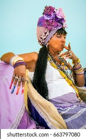 Havana, Cuba -March 13, 2016: Environmetal portrait of a fortune teller lady, a colorful character in Old Havana, Cuba, with super long fingernails, in traditional costume and smoking a cigar.