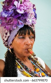Havana, Cuba -March 13, 2016: Portrait of a fortune teller lady, a colorful character in Old Havana, Cuba in traditional costume and smoking a cigar.