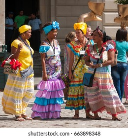 Havana, Cuba - March 13, 2016: Cuban women in traditional clothing and carrying baskets of flowers called 'Costumista' or 'Flower girls' reviving the colonial times in San Francisco Square, Old Havana