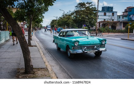 Havana / Cuba - March 19, 2016: 50s style car with protruding headlights and sharp fins riding along in the quiet Vendado neighborhood.