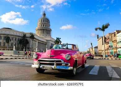 Havana, Cuba - March 2017: A classic pink oldtimer in front of the Capitolio in Havana. Havana is the capital of Cuba.