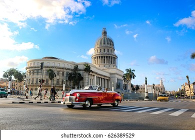 Havana, Cuba - March 2017; A red oldtimer in front of the Capitolio in Havana. Havana is the capital of Cuba.