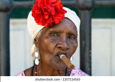 HAVANA, CUBA - MARCH 2019: Portrait of african cuban woman smoking cigar.