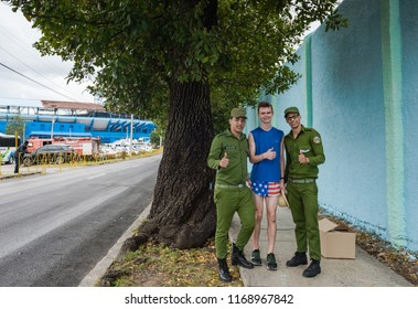 Havana, Cuba / March 22, 2016: American tourist, dressed in patriotic shorts, gives a thumbs up with two Cuban soldiers dressed in uniform fatigues.
