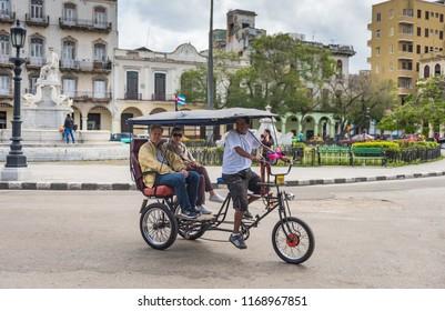 Havana, Cuba / March 22, 2016: Tourists explore Old Havana aboard a bicycle rickshaw.