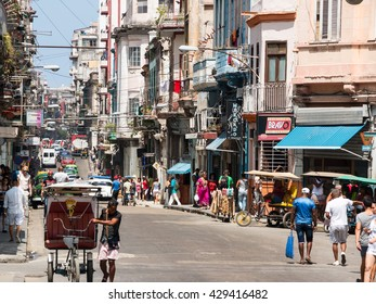 HAVANA, CUBA - MAY 15, 2016: Street scene with bicycle taxi and tourists in downtown Havana, Cuba.