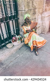 HAVANA, CUBA - MAY 15, 2016: Woman in traditional Cuban dress, posing with a cigar on the streets of Havana, Cuba.