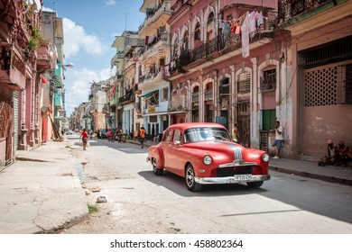 HAVANA, CUBA - MAY 15, 2016: Classic red American car being used as a taxi in downtown Havana, Cuba, with locals.