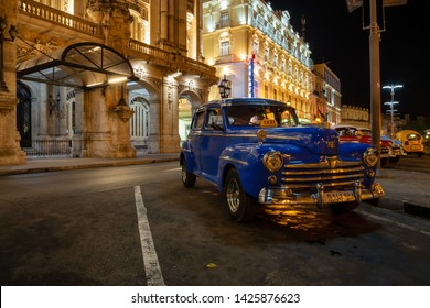 Havana, Cuba - May 17, 2019: Classic Old American Car in the streets of the Old Havana City during a vibrant night after sunset.
