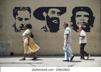 HAVANA, CUBA - MAY, 2011: Cuban people walk in front of stencil billboard featuring Julio Antonio Mella, Camilo Cienfuegos, and Che Guevara, three leaders of the Communist Revolution.