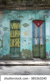 HAVANA, CUBA - MAY 31, 2014: An old house in Central Havana painted with the Cuban flag and a Viva Cuba Libre writing