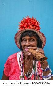 Havana, Cuba - May; A cuban woman holding huge cigar in order to smoke in Havana, Cuba