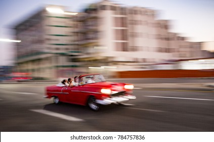 Havana, Cuba Nov 18, 2017 - 1950's era Chevy is motion-blurred as it drives down road past an office high rise