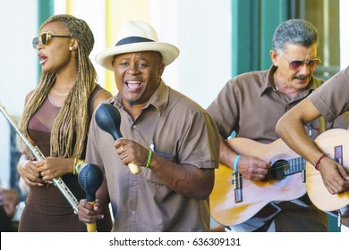 HAVANA, CUBA - NOVEMBER 05, 2016: Latino men musicians dressed in white trousers and brown shirt sing, group plays maracas, guitar near cafe entrance on central street of Havana at summer sunny day
