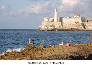 Havana, Cuba - November 11, 2007: fishermen hoping for a catch in Havana Bay, Cuba on a sunny evening with the lighthouse of Morro Castle in the background.