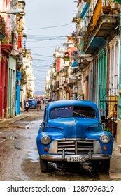 HAVANA, CUBA - NOVEMBER 14, 2017: Typical street scene with people, old cars and colorful buildings. With over 2 million inhabitants Havana is the capital of Cuba and the largest city in the Caribbean