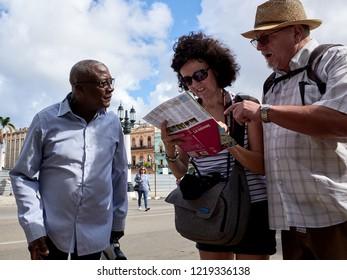 HAVANA - CUBA, NOVEMBER, 15, 2017 Tourists asking for map information to a local cuban in Havana, Cuba