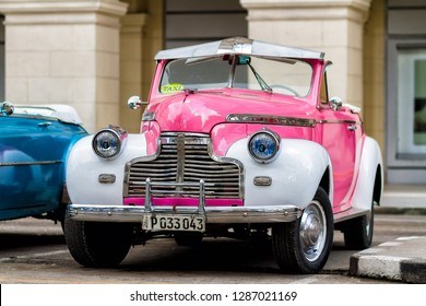 HAVANA, CUBA - NOVEMBER 18, 2017: Old colorful vintage classic car on the streets of Havana, Cuba. American cars due to embargo are still used and serve as a taxi or transportation for tourists.