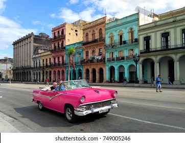 HAVANA, CUBA – NOVEMBER 2017: Fancy pink convertible vintage classic American car with tourists on main street Paseo Marti in front of iconic old colorful colonial houses in Habana Vieja / Old Havana