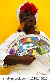 Havana, Cuba - November 26, 2011 : Portrait of a happy cuban woman smoking cigar in front of yellow wall in Havana, Cuba.
