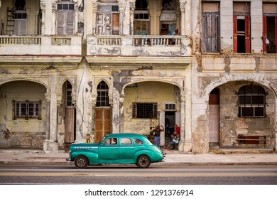 Havana, Cuba - November 29, 2017: Old car passing on Malecon decaying buildings