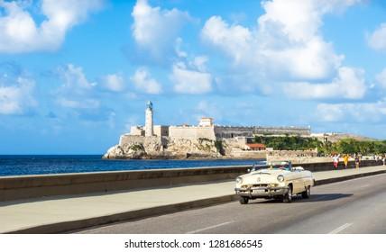 Havana, Cuba - October 03, 2018: American beige 1953 Mercury Monterey convertible  vintage car on the Malecon in the background the  fortress Castillo del Morro in Havana Cuba - Serie Cuba Reportage