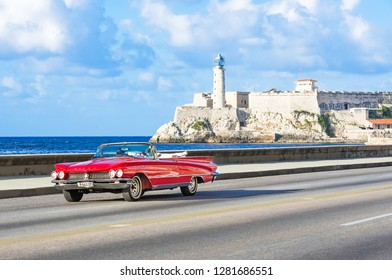 Havana, Cuba - October 03, 2018: American red convertible 1959 Buick Le Sabre vintage car on the Malecon in the background the  fortress Castillo del Morro in Havana Cuba - Serie Cuba Reportage