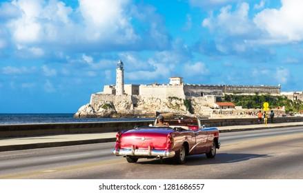 Havana, Cuba - October 03, 2018: American red convertible Buick 50 Super 1954 vintage car on the Malecon in the background the fortress Castillo del Morro in Havana Cuba - Serie Cuba Reportage
