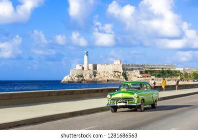 Havana, Cuba - October 03, 2018: American green 1952 Ford Customline vintage car on the promenade Malecon in the background the Castillo Tres Reyes del Morro in Havana City Cuba - Serie Cuba Reportage