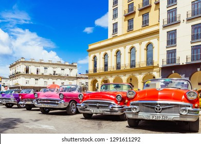 Havana, Cuba - October 03, 2018: American red 1955, 1956 Buick Century convertible, pink 1957 Chevrolet  Bel air convertible and a 1958 Ford Fairlane convertible vintage cars - Serie Cuba Reportage