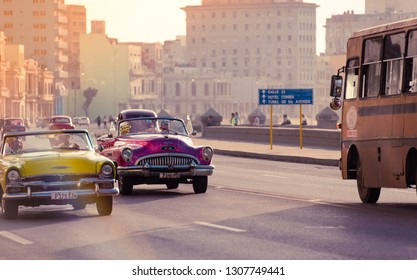 Havana, Cuba - October 03, 2018: American pink 1952 Buick Special and a rare yellow 1954 Plymouth Savoy convertible vintage car drive in the sunset on the Malecon with tourists - Serie Cuba Reportage