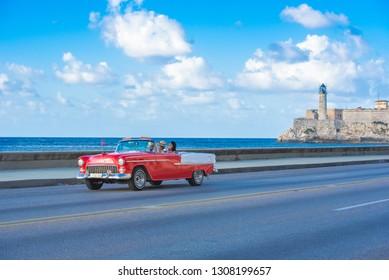 Havana, Cuba - October 03, 2018: American red 1955 Chevrolet Bel air convertible vintage car on the promenade Malecon in the background the Castillo de los tres Reyes del Morro - Serie Cuba Reportage