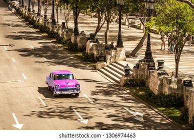 Havana, Cuba - October 04, 2018: Sepia - American pink 1956 Chevrolet Bel Air drives on the street Jose Marti in Havana City Cuba - Serie Cuba Reportage